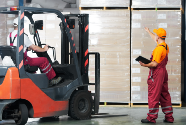 Man in forklift talking to another man while in a warehouse