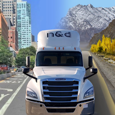 N&D truck driving on road in front of mountains and buildings