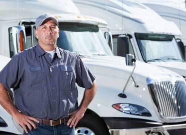 Man standing in front of 2 white 18 wheel trucks