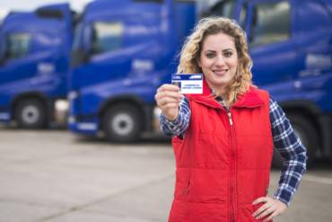 woman showing her cdl drivers license in front of blue trucks