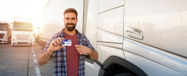 Man holding CDL drivers license in front of truck in rhode island
